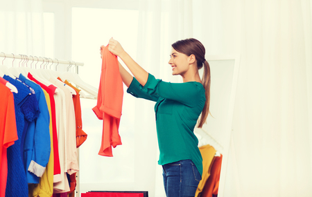 closet: clothing, fashion, style and people concept - happy woman with shopping bags and clothes at home wardrobe