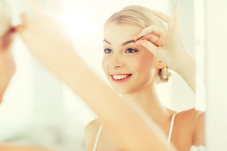 tweezing: beauty and people concept - smiling young woman with tweezers tweezing eyebrow and looking to mirror at home bathroom Stock Photo