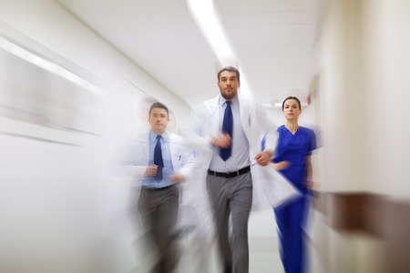 people, health care and medicine concept - group of medics running along hospital (motion blur effect)