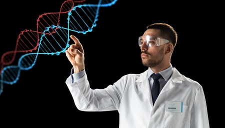 science, genetics and people concept - male doctor or scientist in white coat and safety glasses touching touching virtual projection of dna molecule over black background Stock Photo