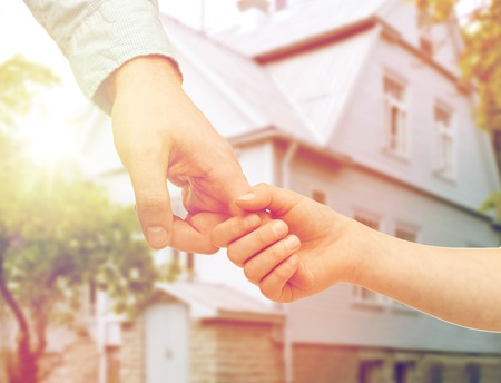 family, home and people concept - father and child holding hands over house background