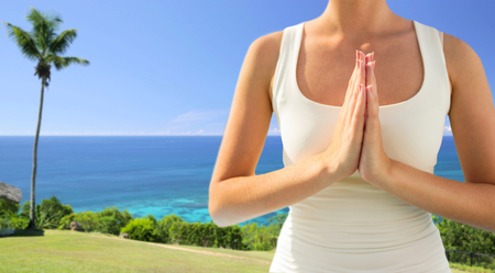 yoga and people concept - close up of woman doing namaste gesture outdoors over exotic natural background with ocean