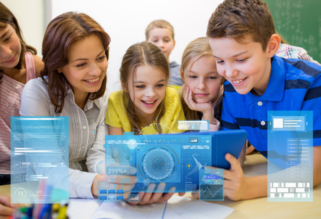 education, elementary school, learning, technology and people concept - group of kids with teacher looking to tablet pc computer in classroom over virtual screens projections photo