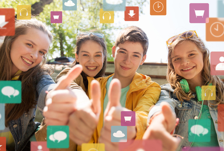 friendship, technology and people concept - happy teenage friends or high school students showing thumbs up with menu icon Imagens