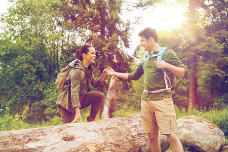 adventure, travel, tourism, hike and people concept - smiling couple with backpacks walking and climbing over fallen tree trunk in woods