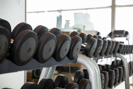 multiple objects: fitness, sport, exercising, weightlifting and bodybuilding concept - dumbbells and sports equipment in gym