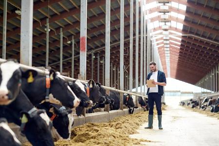 landbouw-industrie, de landbouw, de mensen en veeteelt concept - gelukkig lachende jonge man of boer met klembord en koeien in de stal op melkveebedrijf
