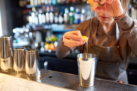 alcohol drinks, people and luxury concept - woman bartender with shaker braking egg and preparing cocktail at bar 版權商用圖片