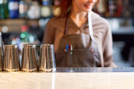 alcohol drinks, people and luxury concept - woman bartender and steel shakers at bar 版權商用圖片