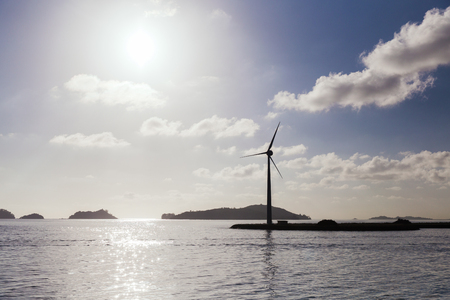 renewable energy, technology and power concept - turbines at wind farm on sea shore