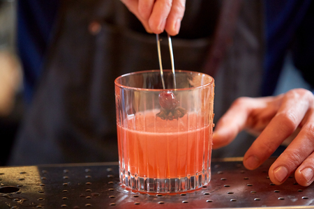 alcohol drinks, people and luxury concept - bartender adding cherry and anise into glass of cocktail at bar