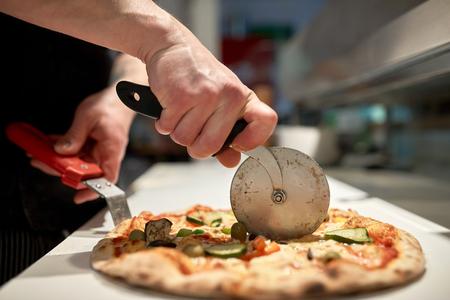 comida, cocina italiana y concepto de cocina - cocine con pizza de corte de corte en pedazos en la pizzería