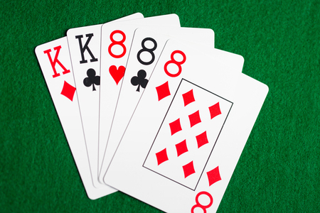games hand: casino, gambling, games of chance, hazard and entertainment concept - poker hand of playing cards on green cloth Stock Photo