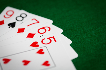 games hand: casino, gambling, games of chance, hazard and entertainment concept - straight poker hand of playing cards on green cloth Stock Photo
