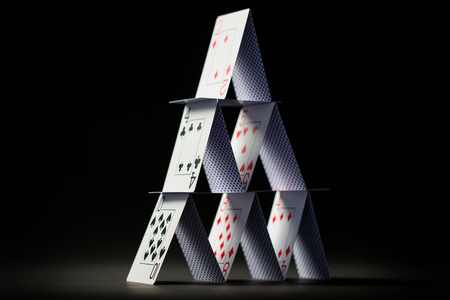 casino, gambling, games of chance, hazard and insecurity concept - house of playing cards over black background Reklamní fotografie