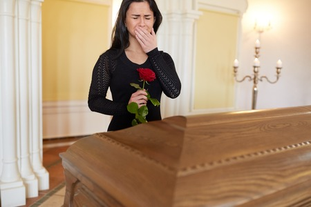 funerary: burial, people and mourning concept - crying unhappy woman with red rose and coffin at funeral in church