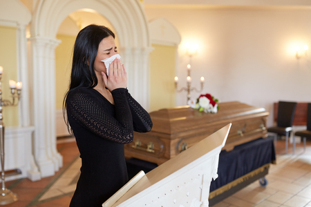 burial, people, grief and mourning concept - close up of sad woman with napkin crying near coffin at funeral in church Stock Photo