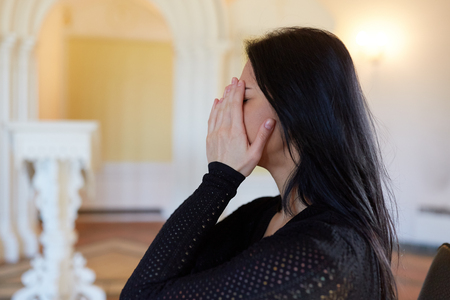 funerary: burial, people and mourning concept - crying unhappy woman at funeral in church