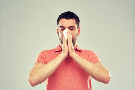 sick man with paper napkin blowing nose Stock Photo