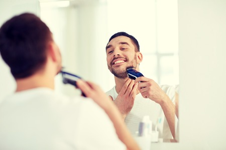 man shaving beard with trimmer at bathroom