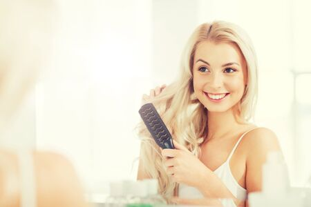 happy woman brushing hair with comb at bathroom Stock Photo