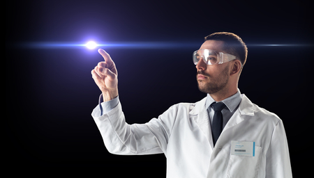 science, future technology and people concept - male doctor or scientist in white coat and safety glasses pointing finger to laser ray over black background