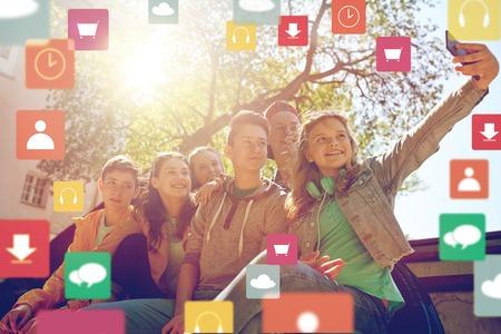 vriendschap, technologie en mensenconcept - groep gelukkige tienerstudenten of vrienden die selfie door smartphone in openlucht over virtuele pictogrammen nemen