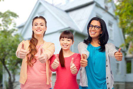 diversity, friendship and people concept - international group of happy smiling different women showing thumbs up over house background