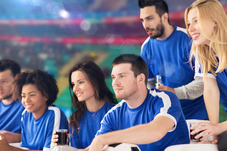 friendship, sport and entertainment concept - happy friends or football fans with drinks watching soccer match ove stadium background