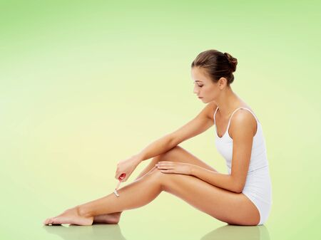 gente sentada: people, beauty and bodycare concept - beautiful woman with safety razor shaving legs sitting on floor over green background
