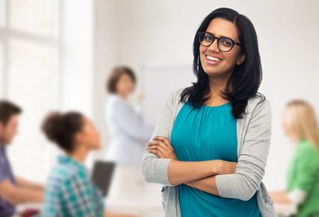 koncepcja edukacji, liceum i ludzi - szczęśliwa uśmiechnięta młoda indyjska kobieta lub nauczyciel w okularach na tle klasy