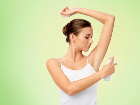 beauty, hygiene and people concept - beautiful young woman applying antiperspirant or spray deodorant over green background