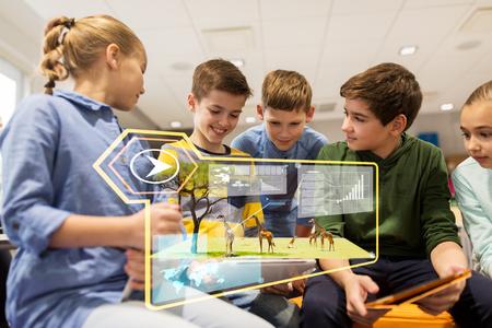 concept de l'éducation, de la technologie et des personnes - groupe d'enfants heureux avec des ordinateurs tablet pc apprentissage à l'école des animaux sauvages sur un écran virtuel