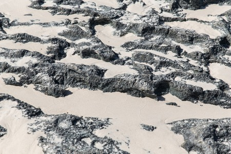 background and texture concept - close up of stone or volcanic rock surface with sand Stock Photo