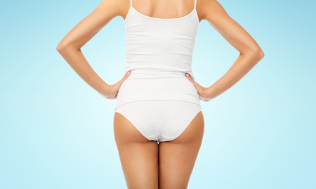 beauty, people and bodycare concept - close up of beautiful young woman body in white underwear from back over blue background Imagens