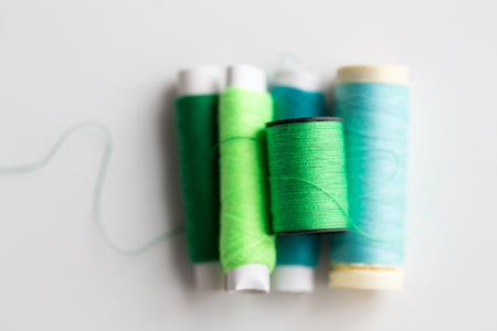 Green and blue thread spools on table