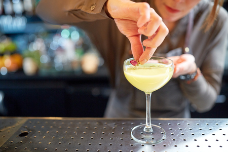 bartender decorating glass of cocktail at bar
