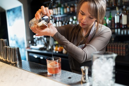barmaid with glass and jug preparing cocktail Banco de Imagens