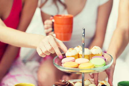 friendship, people, pajama party and junk food concept - close up of friends or teenage girls eating sweets from cake stand at home