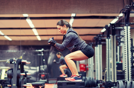 fitness, sport, exercising and people concept - woman doing squats on platform in gym Stock Photo