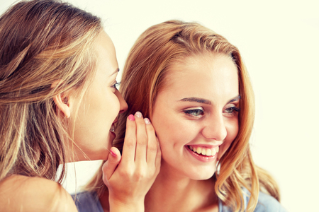 friendship, people, pajama party and communication concept - happy young women gossiping and whispering to ear at home