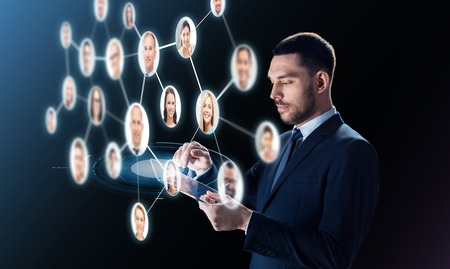 network people: business, people, headhunting, communication and modern technology concept - businessman in suit working with transparent tablet pc computer and contacts network over black background