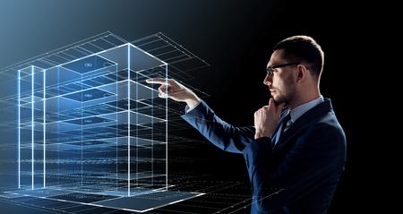 zaken, mensen en toekomstig technologieconcept - zakenman in glazen met virtueel bouwhologram over zwarte achtergrond Stockfoto