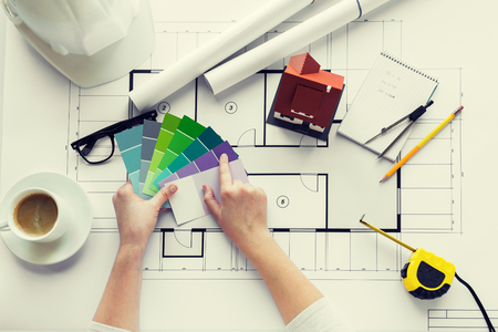 business, architecture, building, construction and people concept - close up of designer hands with color palette and house blueprint Imagens