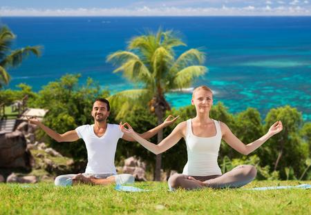フィットネス、スポーツ、瞑想、人々 の概念 - ヨガと瞑想屋外自然バック グラウンドと海の上の幸せなカップル 写真素材 - 78704852