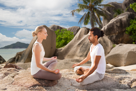 fitness, sport, meditation and people concept - happy couple doing yoga and meditating outdoors over tropical natural background Stock Photo