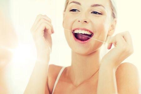 aseo personal: Mujer con seda dental limpiando los dientes en el baño