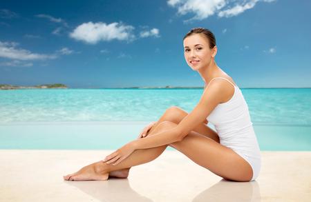夏のビーチで彼女の足に触れる美しい女性