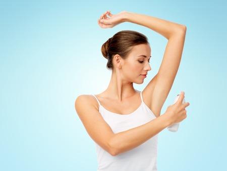 Vrouw met antiperspirant deodorant over blauw