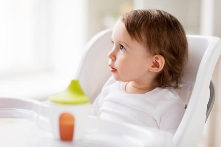 自宅のハイチェアに座っている女の幸せな赤ちゃん 写真素材